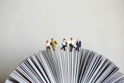 Miniature people: Businessman reading newspaper and sitting on book using as background education or business concept.