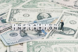 Miniature people businessman standing and wise thinking with cube block combine word Inflation on US dollar money banknote using as economic inflation that money buys less than prior periods.