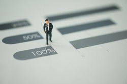 Miniature people : businessman standing on bar chart step from fifty percent to one hundred percent. The concept of financial and Business competition concept using as background.