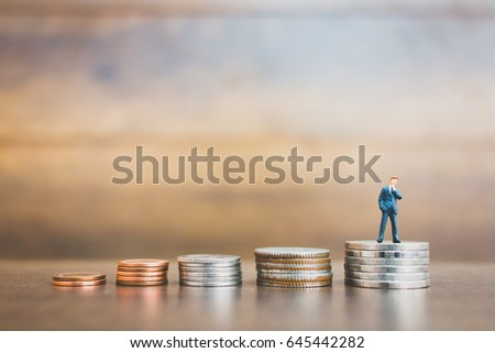 Miniature people businessman standing on money with  wooden background #645442282