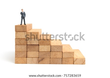 Miniature people: Businessman standing on wood block isolated on white background #757283659