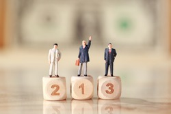 Miniature people: businessman standing on wooden podium with dollar bank note blur background (Financial and Business competition concept)