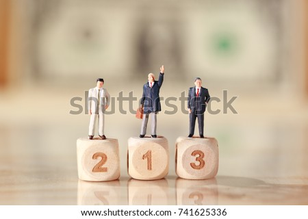 Miniature people: businessman standing on wooden podium with dollar bank note blur background (Financial and Business competition concept) #741625336