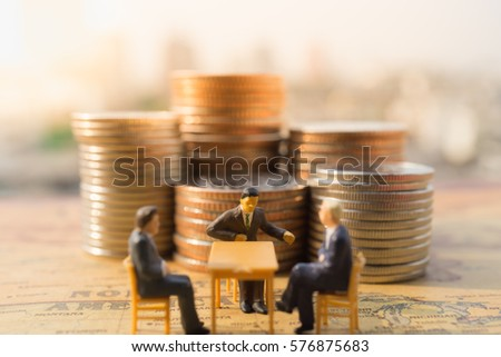 Miniature people : Businessmen meeting in front of stack of coins over vintage map with modern city background. Business and finance concepts.