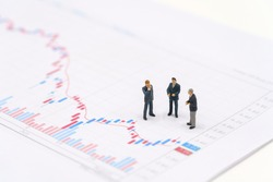 Miniature people businessmen standing on the stock market chart is the background Investment Analysis investment . using as background business concept with copy space and white space.