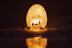 Miniature people child Jesus Christ in the manger with Mary and Joseph in egg sparkle light.Christmas concept.