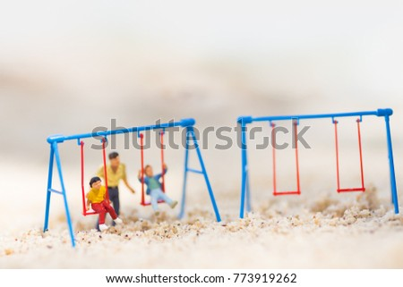 Stock Photo Miniature people : Children are playing swings happily. Father takes care of the back on the sand beach.