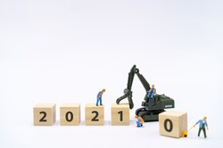 Miniature people Construction worker Manage products with wooden block 2021 on white background using as background Happy new year concept with copy space  for your text or  design.