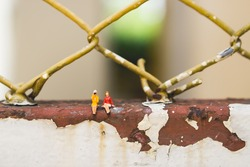 Miniature people couple woman sitting on net used for human resource concept