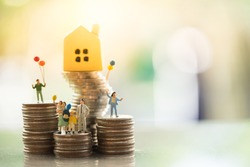 Miniature people: family standing on coins stacks with  house model on the top stack.  concepts. Concept for property ladder, mortgage,real estate investment, money, love and Valentine's day.