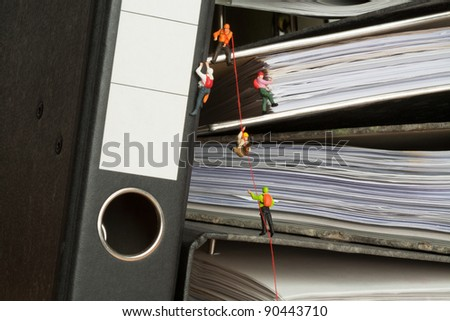 Miniature people group of climbers ascending document binders