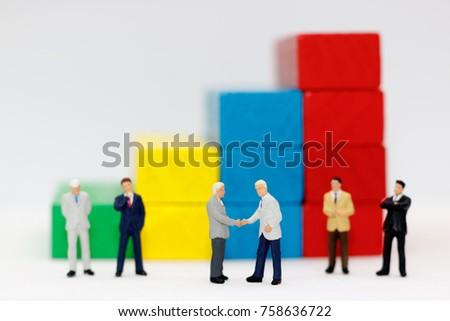 miniature people handshake with ...