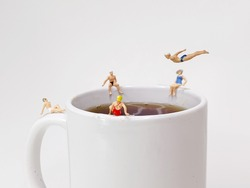 Miniature people hanging around a coffee cup