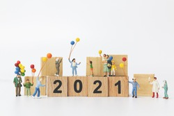 Miniature people : Happy family holding balloon on wooden block number 2021  , Happy new year concept