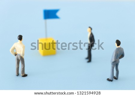 miniature people looking at destination pin sign