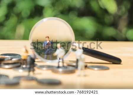 Miniature people: Magnifying glass focusing on the selected candidate on the coins stack, recruitment process, HR, HRM, HRD concepts.