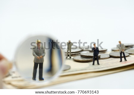 Miniature people: Magnifying glass focusing on the selected candidate on the coins stack and banknote. Recruitment process, HR, HRM, HRD concepts.