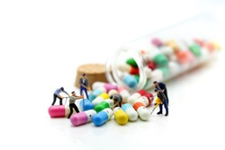 Miniature people : man working on capsule drug using for healthy concept.