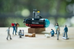 Miniature people of worker loading thing to submarine on wood table with nature background. Selective focus