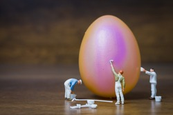 Miniature people :Painter is painting Easter-eggs for Easter day on wooden background