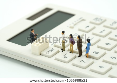 Miniature people Pay queue Annual income (TAX) for the year on calculator. using as background business concept and finance concept with copy space  for your text or  design. #1055988521