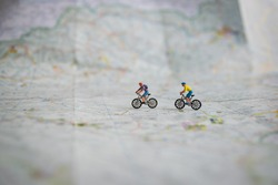 Miniature people pedaling in a map, cycling, mountainbike, sport, outdoor, travel
