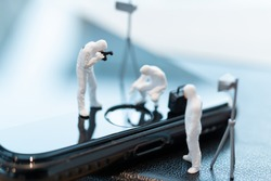 Miniature people : Police And Detective are working on smartphone , Crime scene investigation , Cyber crimes concept