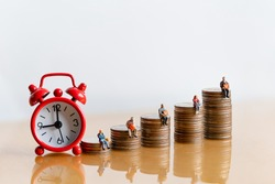 Miniature people: Red alarm clock and elderly people sitting on coins stack. Retirement planning. money saving and Investment. Time counting down for retirement and pension.