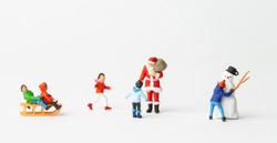 Miniature people: Santa Claus and kids playing fun. Christmas and Happy New Year concept.