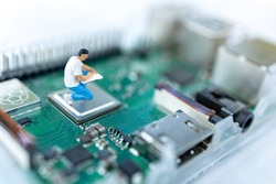Miniature people searching or checking for bugs and issue on microchip, mainboard of computer. Vulnerability search and security system concept.