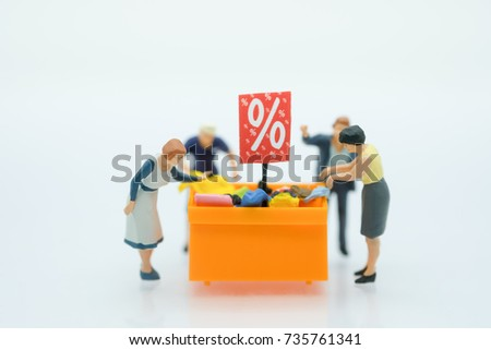 Miniature people: Shoppers with discount tray for shopping discounted items using as background business concept.