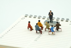 Miniature people sitting on red staples placed on a Book Rankings (list). meeting or Discussion using as background business concept with copy space and white space for your text or  design.