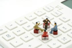 Miniature 4 people sitting on red staples placed on a white calculator. meeting or Discussion using as background business concept with copy space and white space for your text or  design.