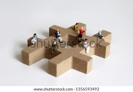 Miniature people sitting on the block of # symbolic trees. #1356593492