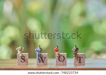 Miniature 4 people sitting on wood word SWOT using as background business concept and Strategy concept with copy space for your text or design.