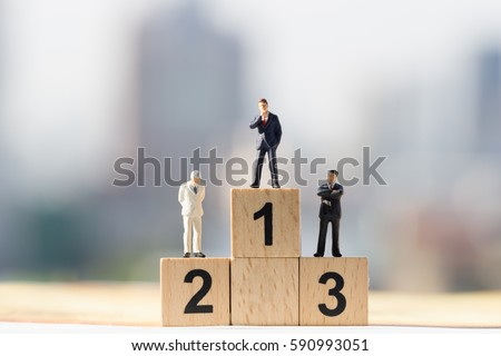 Miniature people: Small businessmen figures standing on wooden podium 1, 2, 3 with cityscape background #590993051
