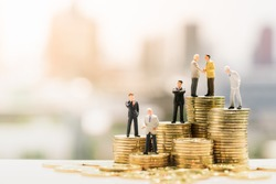 Miniature people: Small businessmen standing on stack of coins, Money, Financial, Business Growth concept.