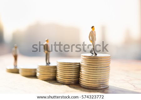 Miniature people: Small figure standing on stack of coin. Money and financial concepts. Foto stock ©