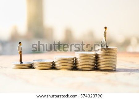 Miniature people: Small figures standing on stack of coin. Money and financial concepts.