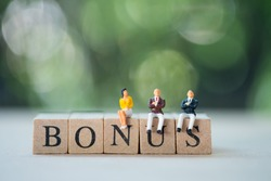Miniature people : staff sitting on wooden block of BONUS for waiting bonus. Bonus prize profit incentive additional compensation concept