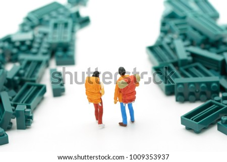 Miniature 2 people stand on The walkway is a block of green jungle or meadow. Means the beginning of the journey To reach the goal. using as background  travel concept with copy spaces for your