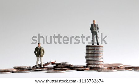Miniature people standing on a pile of coins.