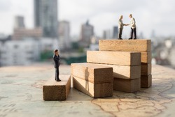 Miniature people: Successive business concept. Businessman thinking on first step of wood stair and two businessmen shaking hands on top step with modern city background.