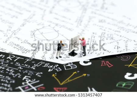 Miniature people : teacher and friend with Math problems on graph paper,formula arithmetic using for concept of World Maths Day.