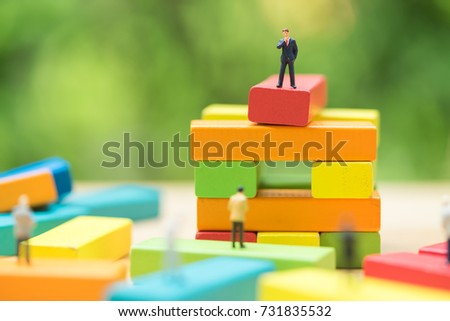Miniature people: the recruiter on top of wooden blocks stack for finding the candidates below, recruitment process, HR, HRM, HRD concepts.
