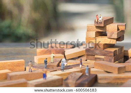 Miniature people: the recruiter sitting on top of wooden blocks stack for finding the candidates below, recruitment process, HR, HRM, HRD concepts.
