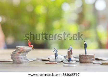 Miniature people: the recruiter sitting on top of wooden blocks stack for finding the candidates on the coins stack, recruitment process, HR, HRM, HRD concepts.