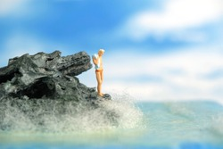 Miniature people toy figure photography. A men standing at a rock getting on beach ready to do cliff jump. Image photo