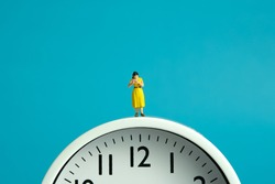 Miniature people toy figure photography. Reading routine concept. A girl student standing read a book above clock. Image photo