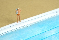 Miniature people toy figure photography. Safety travel concept, Men with swimsuit standing in front of blue face mask. Image photo